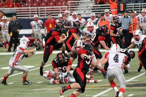 Lamar's Levi Petersen (with ball) hurdles a Lawson defender in 2013 state title game (Photo courtesy of Lamar HS)